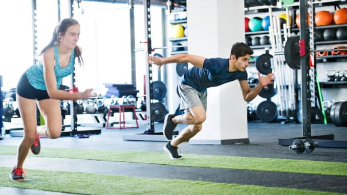 Young fit couple in gym fast running.