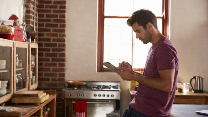 Young man using tablet computer in kitchen, waist up
