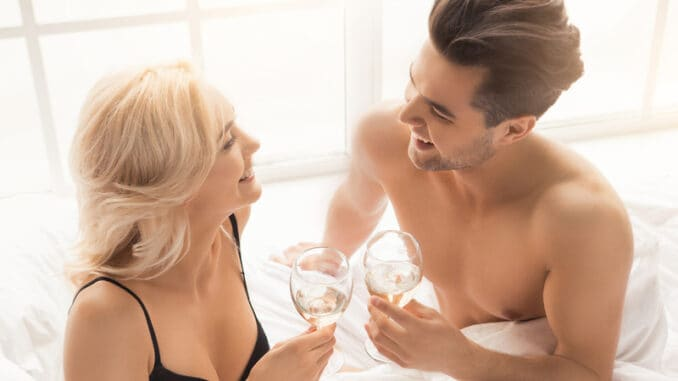 Young couple men and women intimate relationship on bed drinking champagne