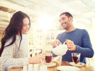 happy couple drinking tea at cafe or restaurant