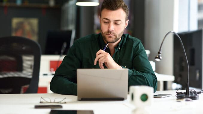 Young man studying with laptop computer on white desk.